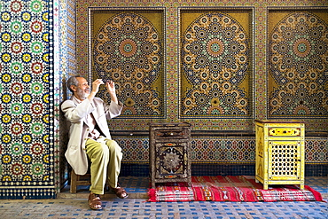 A Distinguished Looking Man Cleans His Glasses While Sitting In Front Of A Spectacularly Patterned Mosaic Wall