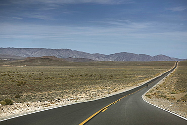 A Person Rides A Motorcycle On A Road Leads To Death Valley Of California