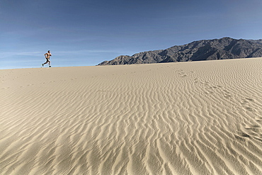A Person Running In Desert Landscape In Death Valley Of California, Usa