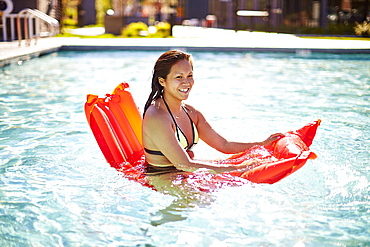 Happy Asian Woman Having Fun With An Air Bed In Pool