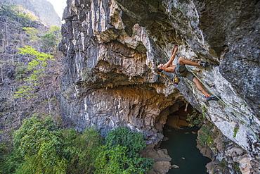 Shirtless Man Climbing Above Cave In Thakhek, Laos