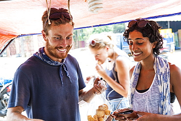 Happy Friends Purchasing Items On A Food Stall