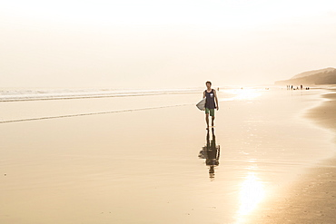 A Male Surfer Walking On The Beach In Nicaragua
