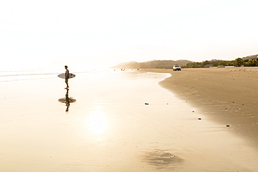 A Male Surfer Stands On The Beach Watching The Waves At Popoyo Beach, Nicaragua