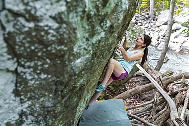 Female Athlete Climbing On Boulder Outside By The River In Maryland