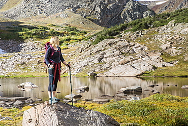 Young Woman Standing On Rock Exploring An Alpine Lake In Colorado