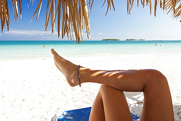 Legs Of A Girl Under The Shadow Of Palm Tree On A Beach In Cuba