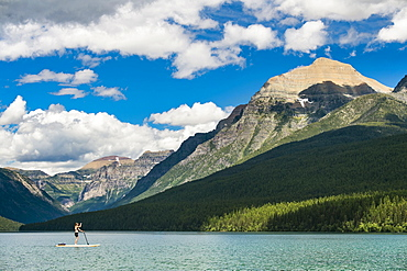 Woman Paddleboarding In Bowman Lake In Montana, Usa