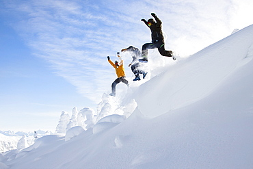 Three Men Jumping Off A Snow Cornice Near Whitefish, Montana, Usa