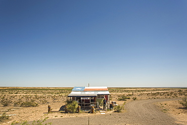 A Solitary Roadside Shack With The Texas Flag Painted On The Roof On An Empty Desert Landscape