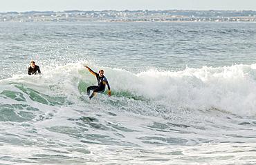 Two Men Surfing On The Oceanic Wave In Pointe De La Torche
