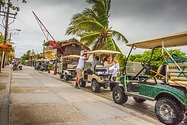 Convoy of golf carts in San Pedro, Belize