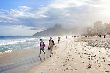 Two Young Women Walking On Ipanema Beach, Rio De Janeiro