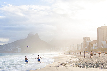 Two Men Playing Soccer In The Surf On Ipanema Beach