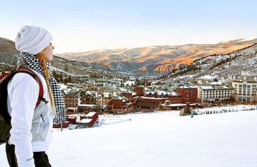 Woman With A Backpack Looks Out Over Beaver Creek Village And Mountains At Dusk
