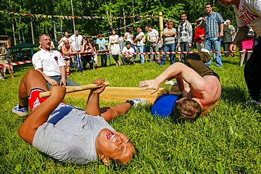 Men Performing Mas-wrestling Game On City Park With Traditional Stick