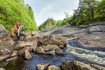 A Rock Climber Crossing A Stream In New York