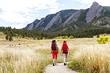 Two Female Hikers Walking On A Trail Beneath The Flatirons In Colorado