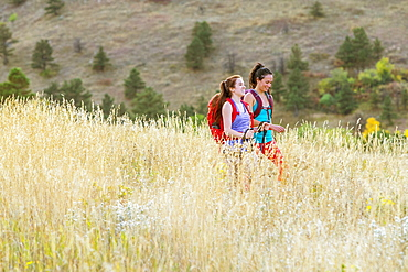 Two Female Hikers Smiling While Walking On A Trail Beneath The Flatirons In Colorado