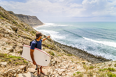 Bodyboarder checks the surf at a spot near Areia Branca, Portugal.