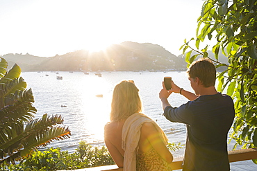 Young adult couple taking cell phone photo of harbor at sunset