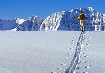 Skier walking through snow in mountains