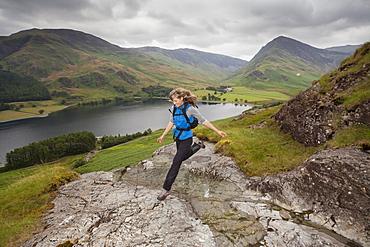 Female hiker bounds between summit rocks