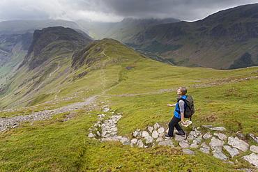 Female hiker walks along cobblestone trail
