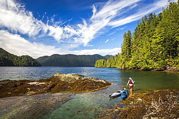 A man pulls two kayaks through shallow, turquoise water along a rocky, forested shoreline.