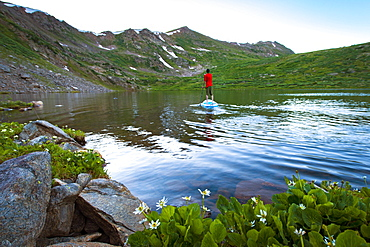 Young male paddleboarding on a high alpine lake in the spring at sunset
