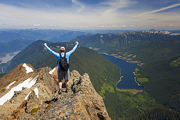 Hiker celebrating in victory pose after climbing Lady Peak in Cheam Mountain Range