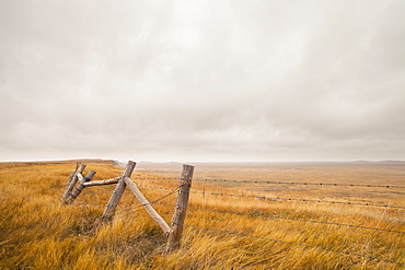 A section of a fence overlooks the plains of South Dakota, United States.