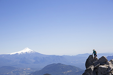 Hiker climbs boulder with snow capped volcano behind