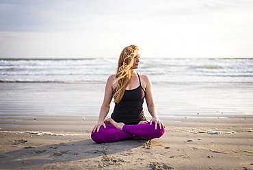 Woman Sitting On Beach Doing Yoga In Rhode Island On Windy Day