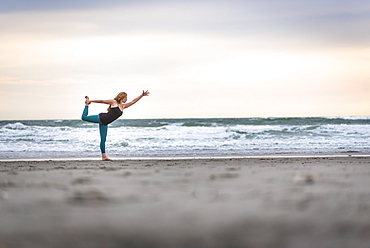 A Woman Doing Yoga On Cloudy Day At The Beach In Rhode Island