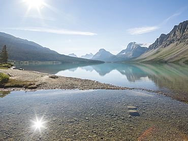 Reflection of mountains and sun in Bow Lake