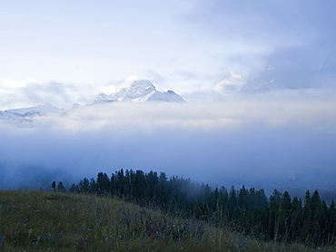 View across alpine meadow to storm lifting off snow-capped peaks