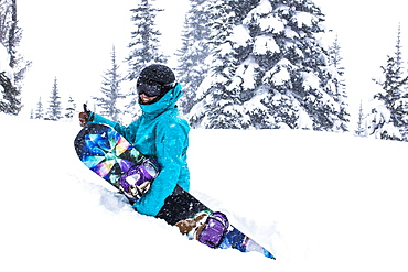 A Female Snowboarder Hikes Through Waist Deep Snow And Gives A Thumbs Up At Whistler Blackcomb Ski Resort