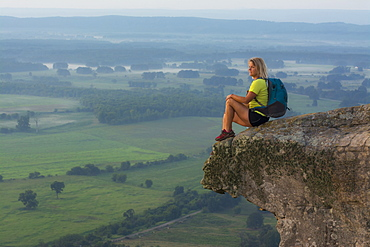 Woman sitting on sandstone overhang watching sunrise from summit of Petit Jean Mountain above Arkansas River Valley