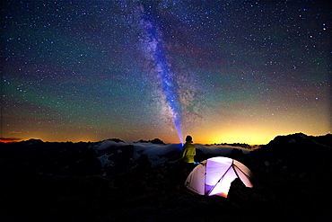 Camper directs Flashlight Along The Milky Way