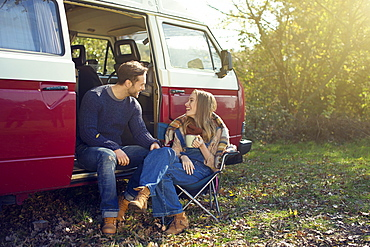 Young couple having coffee in front of caravan