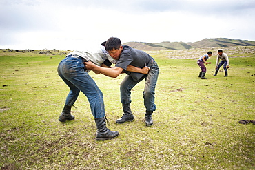 """Day of """"Gou Barih"""". Mongolian fight between young man. Orkhon Valley, Mongolia"""
