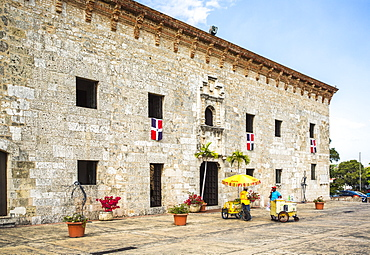 A Historic Stone Fort Building In A Plaza With A Few Colorful Vendors Selling Goods On A Sunny Day