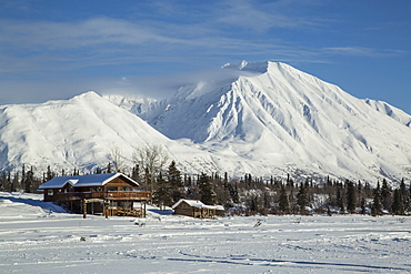 Log cabins in Alaska sit at the base of a frozen lake with snowy mountains in the background.