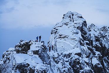 Hikers stand on steep snowy ridge near Tatind, Vestvågøy, Lofoten Islands, Norway