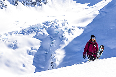 Professional Snowboarder Helen Schettini hikes to a ridge with a glacier in the background on a sunny day in Haines, Alaska.