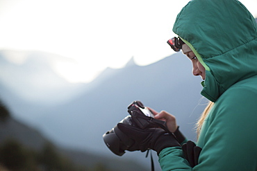 A woman in a down jacket takes photographs at sunrise in Nepal's Everest Region.