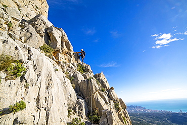 A man rock climbing high on the peak of Puig Campana above the city of Benidorm, Alicante Region, Costa Blanca in Mediterranean Spain.