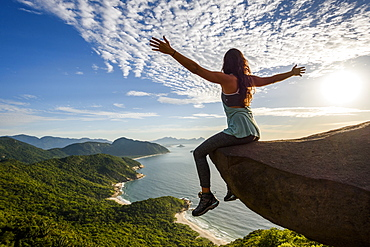 Woman sitting on the edge of the mountain with arms open in Pedra do Telégrafo, Barra de Guaratiba, west side of Rio de Janeiro, Brazil