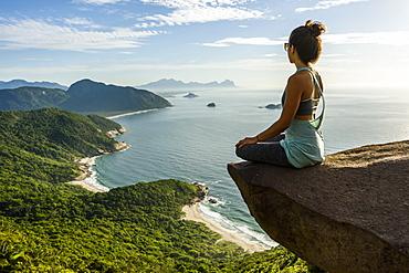 Woman sitting on the edge of the mountain in Pedra do Telégrafo, Barra de Guaratiba, west side of Rio de Janeiro, Brazil